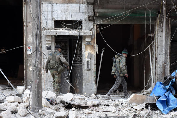 Syrian pro-government forces inspect a building in the al-Maadi district of eastern Aleppo on Sunday after retaking a large part of it from rebel fighters.
