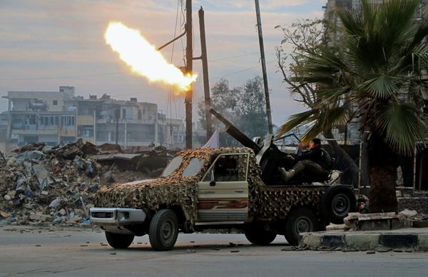 Fighters of the Free Syrian Army fire an anti-aircraft weapon in Aleppo's rebel-held area of Mashhad on Monday, as they battle Syrian government forces.