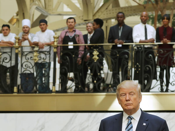 Hotel employees watch then-Republican presidential nominee Donald Trump following a ribbon cutting ceremony at the new Trump International Hotel October 26, 2016 in Washington, D.C.