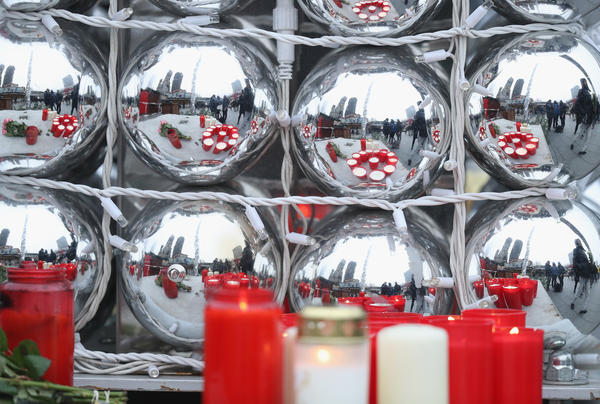 Candles left by mourners are reflected in Christmas balls on Tuesday, near the crime scene where a truck plowed into a crowded Christmas market on Monday. At least a dozen people are dead, and nearly 50 injured