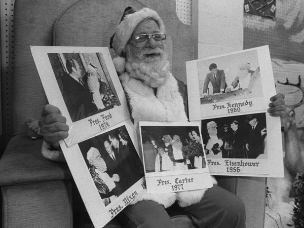 Robert George, recognized as the official Santa to six presidents beginning in 1956, poses with photos of himself and past presidents in this Dec. 11, 1982, photo. He died in 1998.