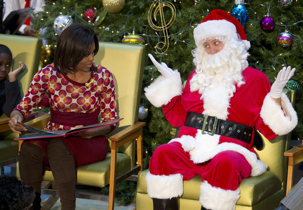 Santa gestures toward first lady Michelle Obama as she reads <em>The Night Before Christmas</em> in 2011 at Children's National Medical Center in Washington.