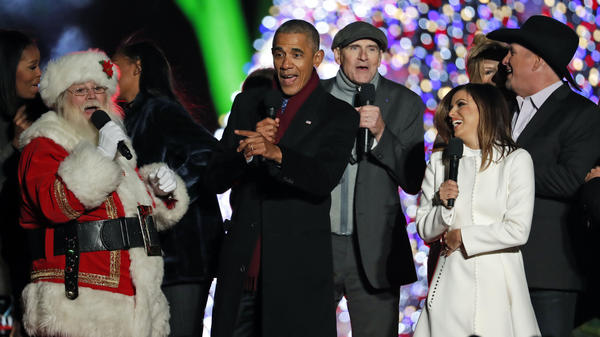 "President Obama sings ""Jingle Bells"" with Santa, James Taylor, Eva Longoria, and Garth Brooks during the lighting ceremony for the 2016 National Christmas Tree."