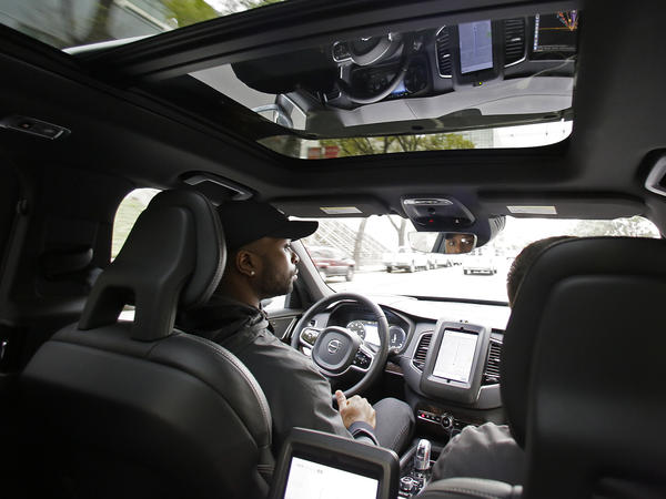 Devin Greene sits in the front seat of an Uber driverless car during a test drive in San Francisco on Dec. 13.