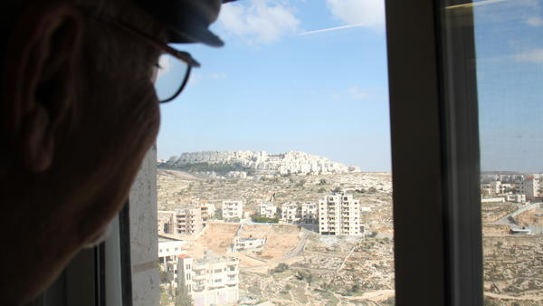 Jad Isaac surveys the Har Homa settlement from his office window. Isaac, director of a Palestinian organization for sustainable development, is encouraged by Secretary of State John Kerry's impassioned defense of the U.N. Security Council's condemnation of the Israeli government's construction of Jewish settlements in the West Bank.