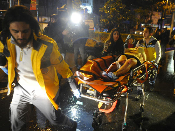 First aid officers carry an injured woman at the site of an armed attack on Sunday in Istanbul. At least 39 people were killed in an armed attack Saturday on an Istanbul nightclub where people were celebrating the new year.