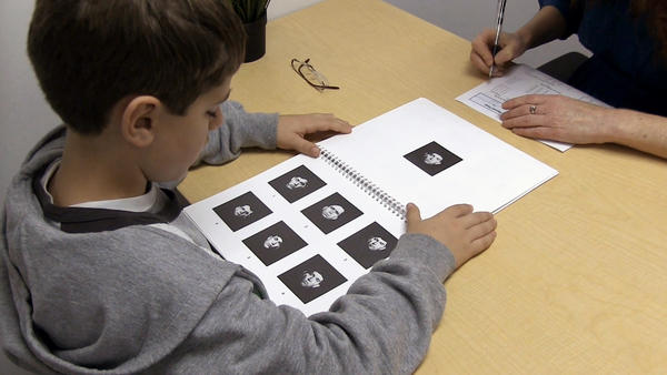 A child takes a facial recognition test in which he is asked to match the face on the top to one of the faces on the bottom.