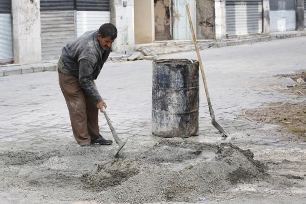 A workman with the U.N. Development Programme to rehabilitate Homs fills a pothole at the beginning of reconstruction in a city that has seen very little so far.
