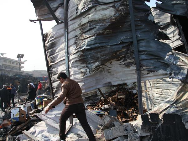 Iraqis inspect the scene of a Sunday car bomb attack at a Baghdad market.