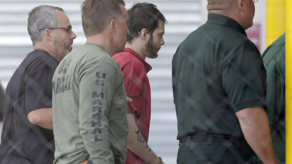 Esteban Santiago (third from left) is returned to jail after his first court appearance Monday in Fort Lauderdale. He is accused of a shooting rampage in which five people were killed.