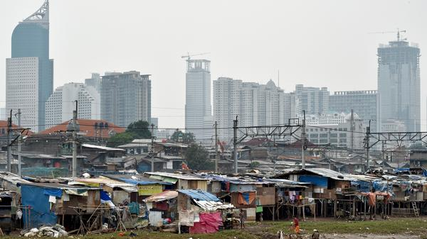 A 2014 photo shows shanty houses on a river bank in Jakarta, Indonesia, where Indonesian President Joko Widodo once pledged to close a fast-growing wealth gap.
