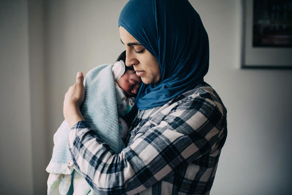 Salma Shabaik holds her newborn son, Ali. When he was born, she held him naked against her bare skin, a practice called kangaroo care. Ali is wearing an ear cap to correct a lop ear.