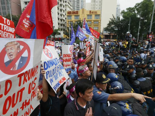 Protesters in Manila confront riot police as they try to march to the U.S. Embassy for a rally to coincide with the inauguration of President-elect Trump on Friday. Left-wing and Muslim activists have asked President Rodrigo Duterte to keep his promise of charting a foreign policy independent of the U.S.