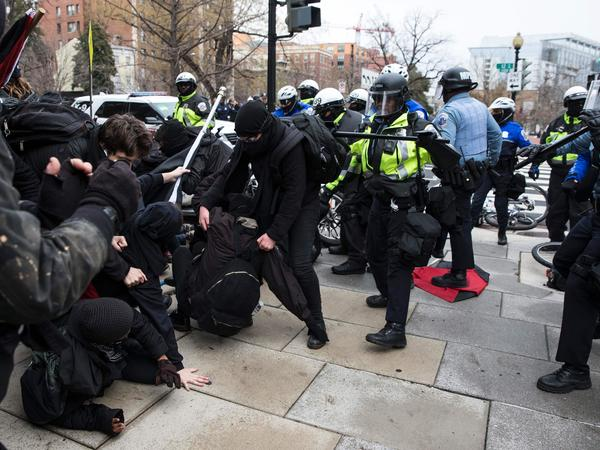 Police officers push a group of demonstrators back in Northwest Washington, D.C., on Friday. Violence broke out in the area among a crowd of several hundred, but the city's interim police chief says protests across the city have been largely peaceful.