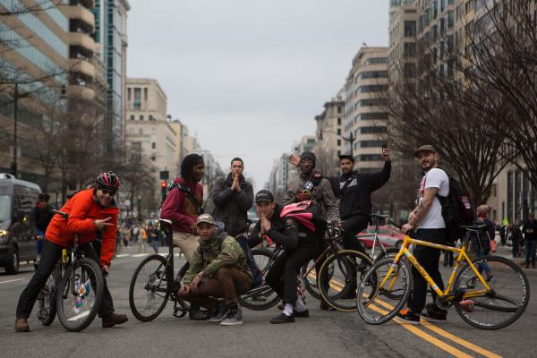 Bicyclists block K Street near McPherson Square, posing for photos in the street.