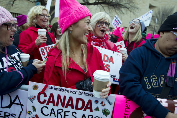 Women with bright pink hats and signs gather early on Saturday in Washington, D.C., for the Women's March on Washington.