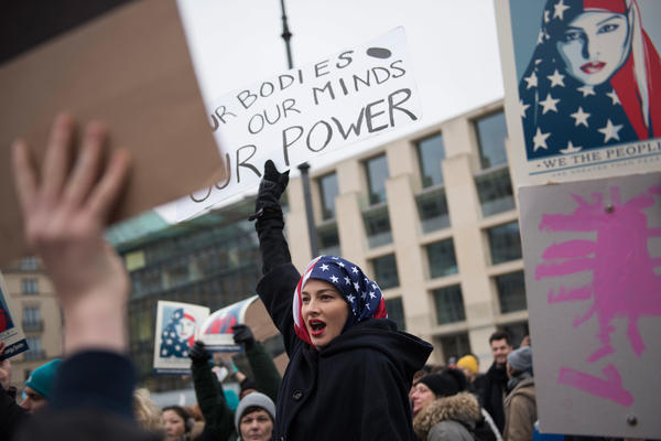 A woman wearing an American flag as a headscarf attends a protest for women's rights and freedom in solidarity with the Women's March on Washington in front of Brandenburger Tor in Berlin, Germany.