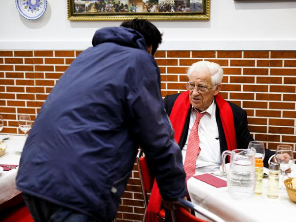 "A dinner patron chats with Father Angel (right), who says that he wants homeless people to ""eat with the same dignity as any other customer."""