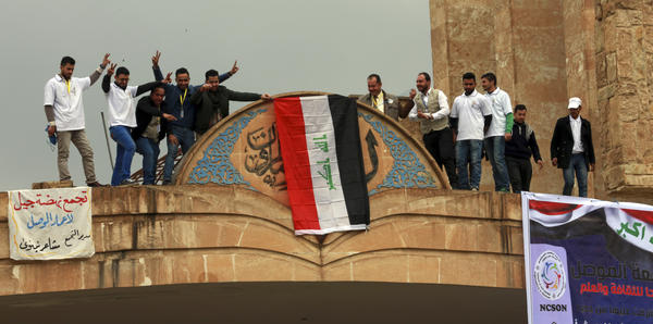 Students at Mosul University place the Iraqi national flag at the entrance on Sunday after it was liberated from Islamic State militants. The Iraqi military, supported by the U.S., has retaken the eastern part of the city. ISIS still holds the western part of Mosul, its last major stronghold in Iraq.