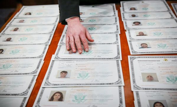 Before the official ceremony, immigrants double-check their certificates of citizenship for any incorrect information.