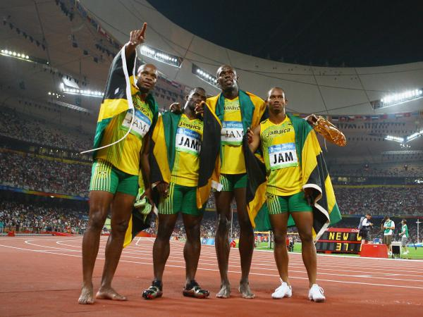 Jamaica's (left to right) Asafa Powell, Nesta Carter, Usain Bolt and Michael Frater celebrate their gold medal after the men's 4x100-meter relay final in Beijing in 2008. With Wednesday's announcement, the team will have to return those medals.