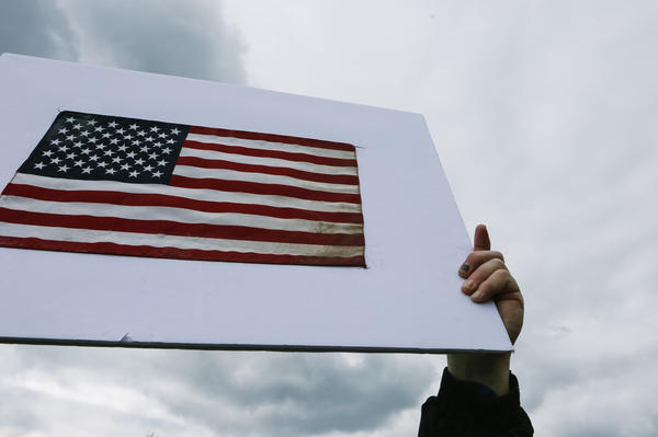 A demonstrator holds up a sign that featured an American flag on one side and messaging supporting abortion rights opponents on the other.