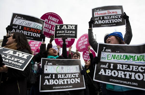 Both abortion rights opponents and abortion rights supporters protest outside the Supreme Court during the 44th annual March for Life.