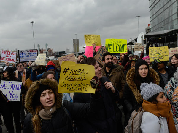 Protesters rally outside Kennedy International Airport to protest Trump's executive order on Saturday. New York City officials and immigrant advocates are holding are also holding a vigil at the airport Saturday evening.