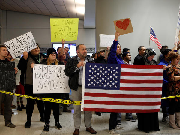 Demonstrators at Dallas-Fort Worth International Airport gather on Saturday to protest President Trump's executive order temporarily barred refugees and citizens of seven countries.