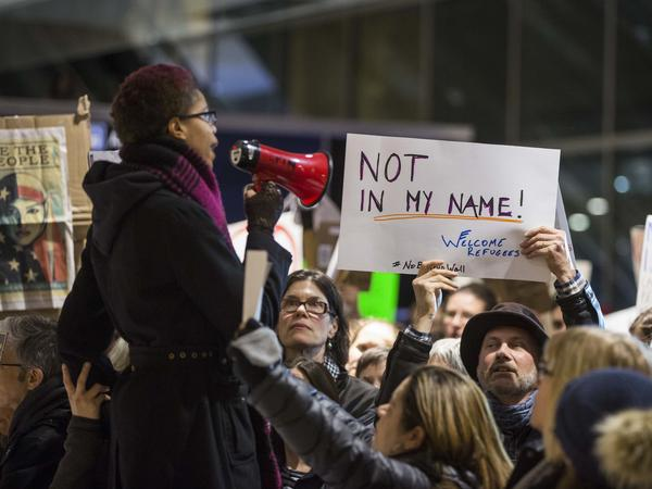 A woman uses a megaphone to address a crowd of protesters at Boston's Logan International Airport on Saturday.