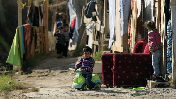 A Syrian refugee boy plays outside his family's tent in a Syrian refugee camp in the town of Zahrani, Lebanon, in December. Some 1 million Syrians live in Lebanon as refugees, according to the U.N.