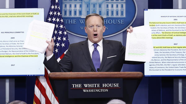 Trying to prove a point that little has changed, White House press secretary Sean Spicer holds up highlighted papers about the National Security Council. But that's not quite true.
