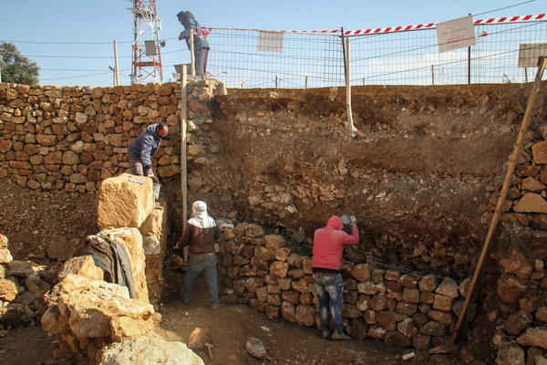 Palestinian workers employed by the Israeli army's archaeology unit lay mortar to reinforce a row of stones, preparing the site as a tourist destination.