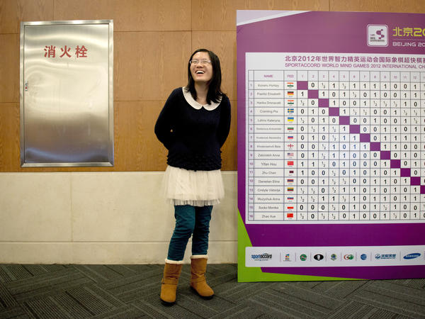 """Hou Yifan of China stands beside a scoreboard following her win in a """"blinfold"""" chess tournament at the Beijing 2012 World Mind Games in Beijing."""