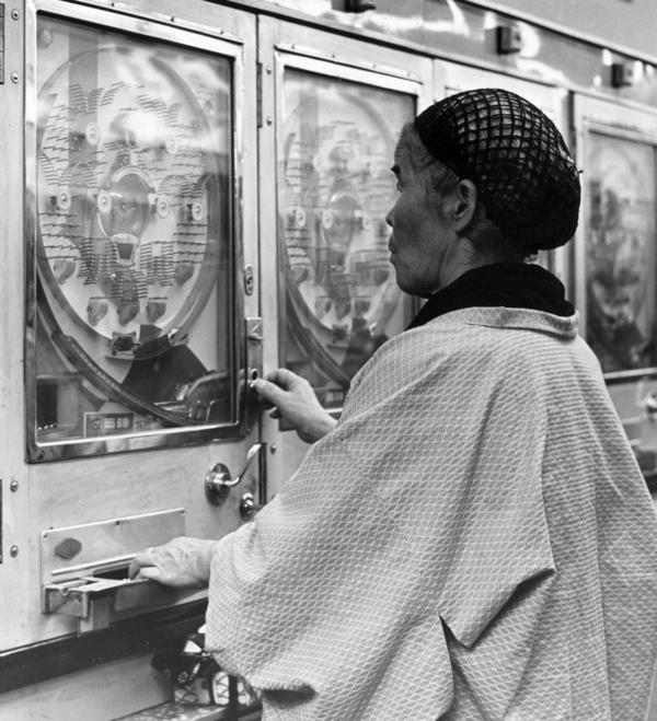 A woman gambles in a Japanese pachinko parlor circa 1955.