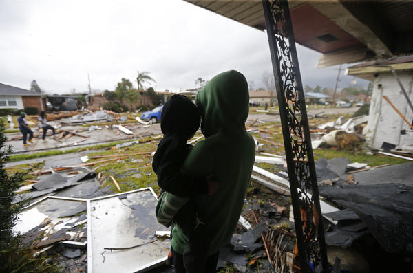 Eshon Trosclair holds her son Camron Chapital on Tuesday after a tornado tore through while they were inside their home in the eastern part of New Orleans. The National Weather Service says at least three confirmed tornadoes touched down, including one inside the New Orleans city limits.