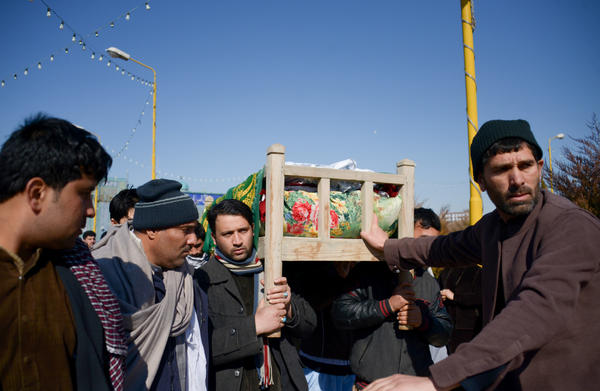 Mourners carry the coffin of one of six Afghan employees of the Red Cross killed in an attack this week in a remote northern province.