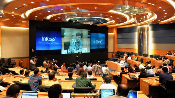 Members of the Indian media watch Rajiv Bansal, then the CFO of Infosys, during the announcement of the company's first quarter results in July 2014 in Bangalore. Indian software services firms draw tens of billions of dollars in revenue from U.S. contracts each year, and that's partly reliant exporting computer science talent on H-1B visas.