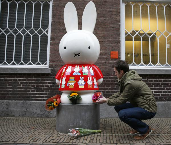 People put flowers at Miffy's statue outside the Nijntje Museum in the Dutch city of Utrecht on Friday, commemorating the death of Dick Bruna.