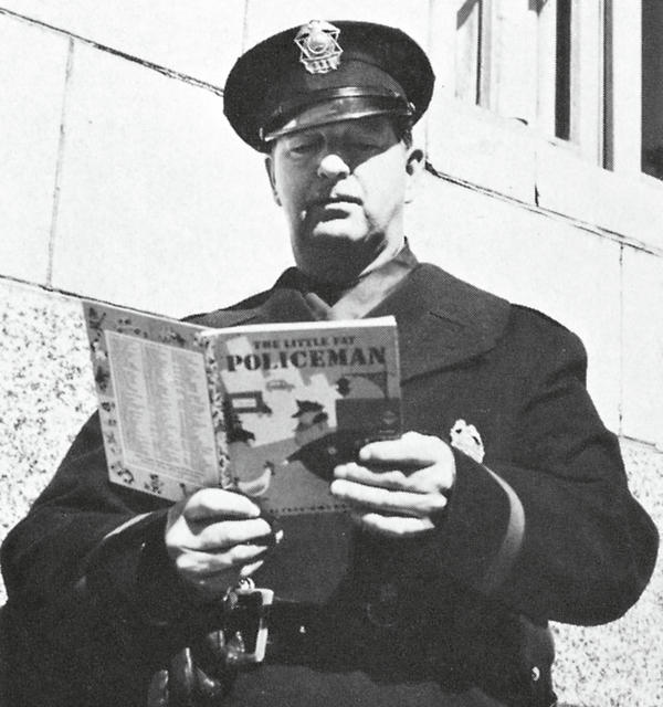 Officer Renny Hoogerhuis poses with a copy of <em>The Little Fat Policeman. </em>The 1950 Little Golden Book was given to every rookie officer on the New York police force in 1955.