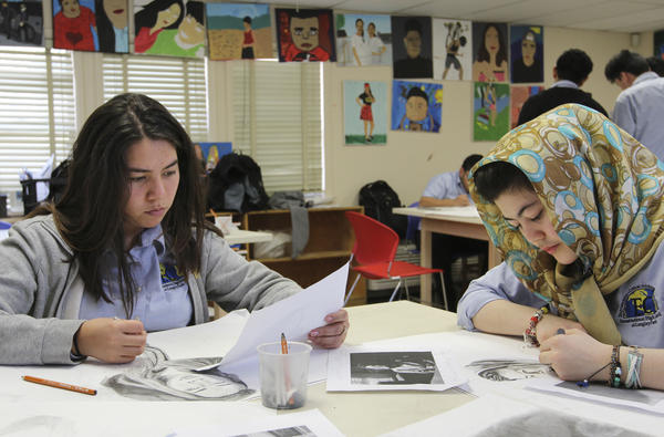 Two talented young artists — Stefany Novoa (left), 16, and Frishta Wassl, 14 — work on self-portraits in Christine Wilkin's art class.