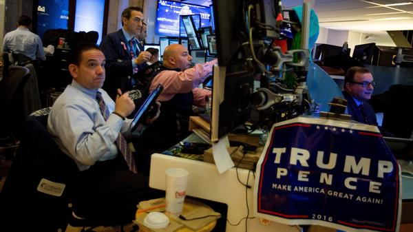 A campaign sign for President Trump and Vice President Pence hangs on a desk while traders work before the opening bell of the New York Stock Exchange the day after the 2016 election.