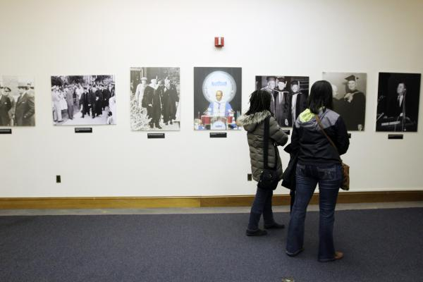 Visitors view historical photographs at the Howard University Museum in Founders Library.