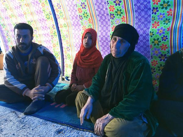 Amsha Mohammad (right) sits with her son Samir Khalil and a grandchild in a tent at a camp for people displaced from Mosul, Iraq. This week, a trickle of people fleeing the city turned into a steady stream of about 4,000 a day.