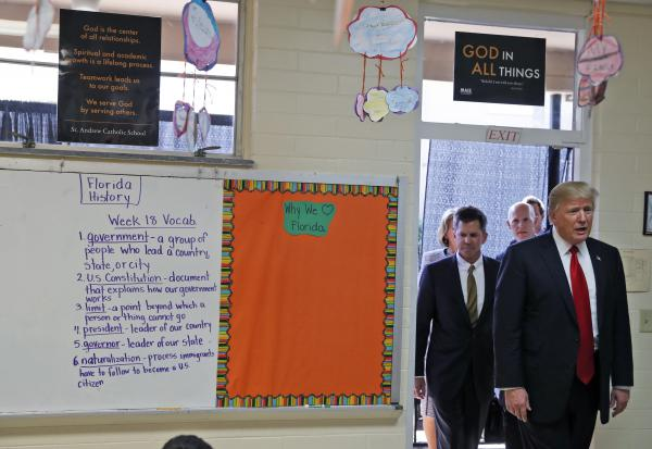 President Donald Trump enters Jane Jones' fourth grade class during a tour of Saint Andrew Catholic School in Orlando, Fla.