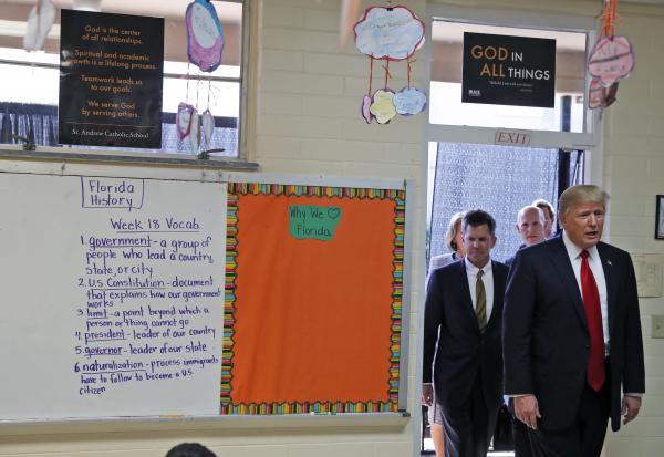President Donald Trump enters Jane Jones' fourth grade class during a tour of Saint Andrew Catholic School in Orlando, Fla.