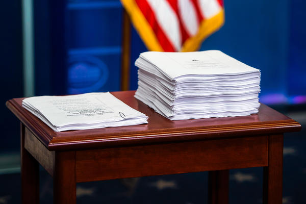 On the right, a print-out of the Affordable Care Act. On the left, a copy of the plan to repeal and replace it.