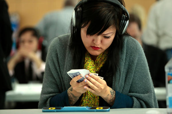 Memory athletes like Sue Jin Yang — competing here in the 17th annual USA Memory Championship in New York City in 2014 — wear headphones to block out distractions as they memorize the order of decks of cards.