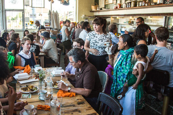 Minara Begum (foreground, far right), holds her daughter Laki while talking to customers at the first Bandhu Gardens pop-up dinner at Rose's Fine Food, a women-owned diner in Detroit, in July 2016.