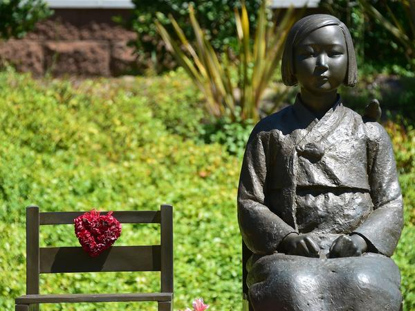 The Comfort Woman statue, with bird on shoulder, beside an empty chair symbolizing survivors who are of an old age without having yet witnessed judgement, in Glendale, California.